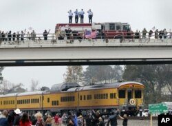 Firefighters stand on their truck and salute along with other attendants on an overpass as the train carrying the body of former president George H.W. Bush travels past on the way to Bush's final internment Dec. 6, 2018.