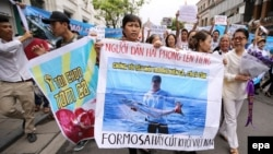 FILE - Vietnamese protesters hold a banner reading 'We love the sea, fish and shrimp. Formosa get out' during a rally denouncing recent mass fish deaths in Vietnam's central province, in Hanoi, Vietnam, 01 May 2016.