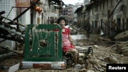 A woman sits on the ruins after typhoon Nepartak swept through Minqing county, Fujian province, China, July 10, 2016.