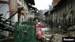 Une femme est assise sur les ruines après le passage du typhon Nepartak qui a balayé le comté de Minqing dans la province du Fujian, en Chine, 10 juillet, 2016. REUTERS / Stringer REUTERS