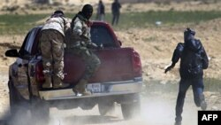 Libijski pobunjenici pod paljbom Gadafijevih snaga na frontu nadomak grada Ajdabije, južnoe od Bengazija.