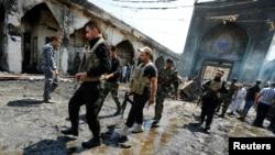 什叶派武装人员在发生爆炸的巴格达以北一处清真寺现场(2016年7月8日)