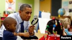 Tổng thống Mỹ Barack Obama cầm kính lúp chơi trò chơi với các bé tại trung tâm dạy học sớm College Heights ở Decatur 14/2/2013.