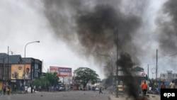 Quelques personnes marchent à proximité d'un pneu brûlé par des manifestants dans la rue dans la capitale Kinshasa, RDC, 19 janvier 2015.epa/ STR