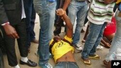 Manifestante espancado pela polícia, na Avenida Joaquim Kapango