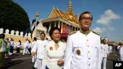 FILE PHOTO - Opposition leader of Cambodia National Rescue Party Sam Rainsy, foreground, walks together with his wife Tioulong Saumura after attending a celebration marking the 10th anniversary of Cambodian King Norodom Sihamoni's coronation, in front of the Royal Palace, in Phnom Penh, Cambodia, Wednesday, Oct. 29, 2014. In a rare public speech, Cambodia's King Norodom Sihamoni urged his compatriots to be united for the sake of the nation. (AP Photo/Heng Sinith)