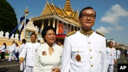 In this file photo taken on Oct. 29, 2014, Sam Rainsy, acting president of the outlawed Cambodia National Rescue Party (foreground) walks together with his wife Tioulong Saumura, after attending a celebration marking 10th anniversary of King Sihamoni, in Phnom Penh.