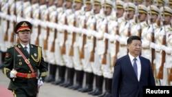 Presiden China XI Jinping memeriksa barisan kehormatan dalam upacara menyambut tamu negara, Presiden Nigeria Muhammadu Buhari (tidak nampak dalam gambar) di Beijing, China (Foto: dok).