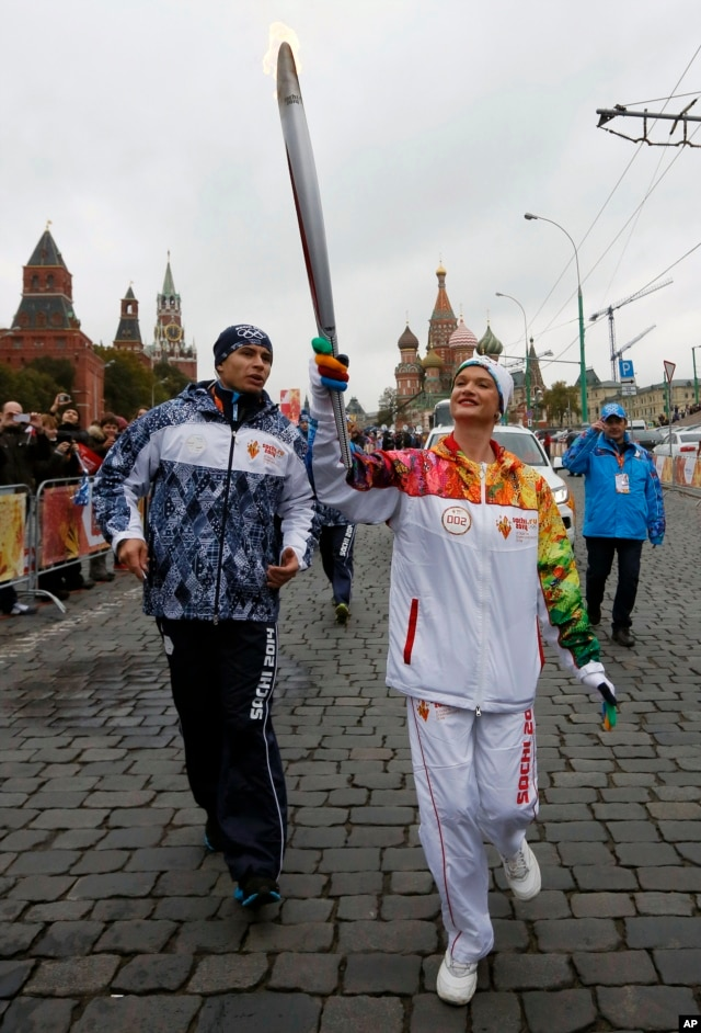 The great Russian artistic gymnast Svetlana Khorkina holds a torch during a relay for the Sochi Winter Olympic Games in Moscow, Russia, Oct. 7, 2013.
