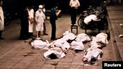 FILE: Medical workers at Beijing's Fuxingmen Hospital look at bodies of protesters killed by soldiers around Tiananmen Square on June 4, 1989.
