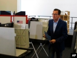 FILE - Gov. Dannel P. Malloy prepares to submit his ballot for the primary election at a polling place in Hartford, Connecticut, Aug. 14, 2018.