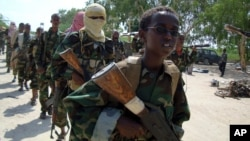 FILE - A youth leads a group of hard-line Islamist al-Shabab fighters as they conduct military exercises in northern Mogadishu's Suqaholaha neighborhood, Somalia, Jan. 1, 2010.