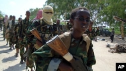 FILE - A youth leads a group of hard-line Islamist Al Shabab fighters as they conduct military exercises in northern Mogadishu's Suqaholaha neighborhood, Somalia, Jan. 1, 2010.