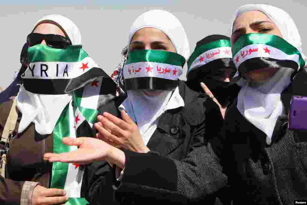 Syrians living in Jordan take part in a protest against Syria's President Bashar al-Assad in front of the Syrian embassy in Amman, March 29, 2013.