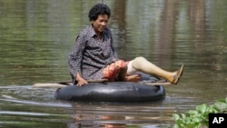 A Cambodian woman rides on a tire tube in a flooded road in Kampong Thom province, about 120 kilometers (75 miles) north of Phnom Penh.