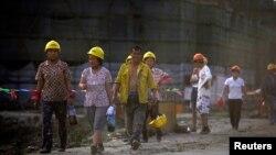 农民工收工后离开上海某居民区的建筑工地。(资料照)