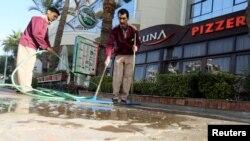 Dua orang pekerja berupaya membersihkan noda darah di tepi jalan dekat hotel Bella Vista Hotel di Hurghada, Mesir (9/1).