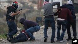 Beberapa polisi Israel yang menyamar, menahan demonstran Palestina dalam aksi protes di Ramallah, Tepi Barat (13/12).
