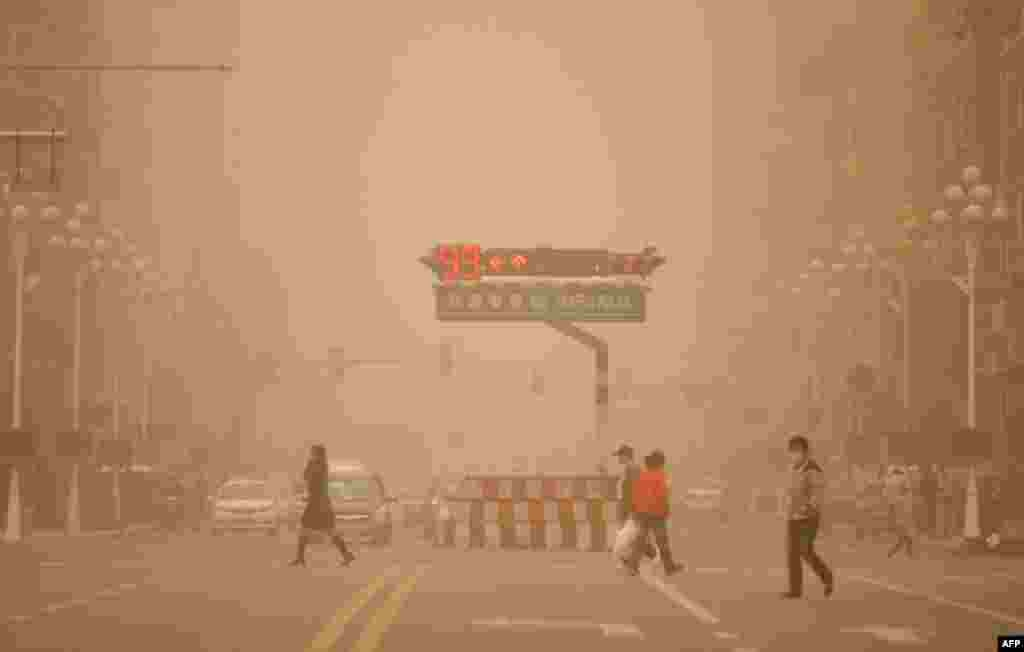 May 12: Residents walk across a junction during a sandstorm in the northern city of Harbin, China. (REUTERS/China Daily)