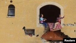 Imagem de arquivo - meninas palestinianas à janela de uma casa que tinha sido bombardeada durante a guerra dos 50 diasna Faixa de Gaza. Março 10, 2015