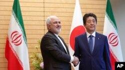 Thủ tướng Nhật Bản Shinzo Abe (phải) bắt tay Ngoại trưởng Iran Mohammad Javad Zarif trong một chuyến thăm của người đứng đầu ngành ngoại giao Iran tới Tokyo hôm 16/5. Ông Abe dự định sẽ đi thăm Iran trong tuần tới.
