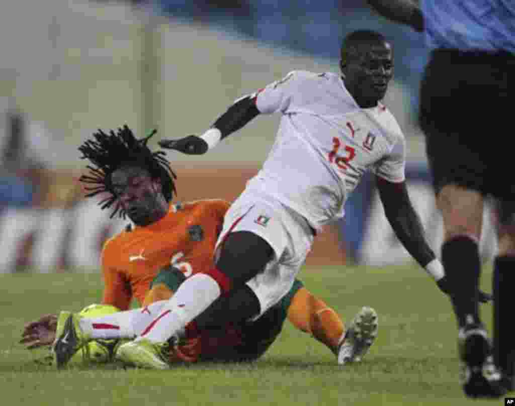 Jean-Jacques Gosso Gosso (L) of Ivory Coast fights for the ball with Thierry Tazemeta of Equatorial Guinea during their quarter-final match at the African Nations Cup soccer tournament in Malabo February 4, 2012.