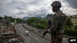 """FILE - A Brazilian army soldier stands guard over the """"Linha Amarela"""" (yellow line) road during a joint operation at """"Cidade de Deus"""" (City of God) favela in Rio de Janeiro, Feb. 07, 2018."""