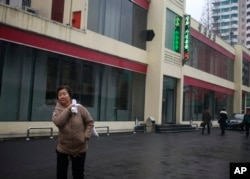 "FILE - In this Dec. 21, 2018, photo, a North Korean woman walks outside Bugsae Shop, also known as the ""Singapore Shop,"" in Pyongyang. Business is booming at such shops, which sell everything from Ukrainian vodka to brand-name knock-offs from China. The stores stock many of the very things U.N. sanctions banning trade in luxury goods are intended to block."