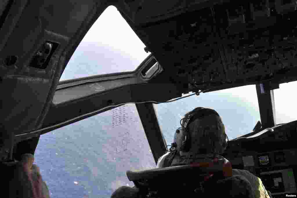 A crew member sits in the cockpit of a Royal New Zealand Air Force patrol aircraft as it continues searching in the southern Indian Ocean for Flight MH370, April 1, 2014.