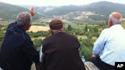 Residents of Güveççi, Turkey, look across the valley to Syria, June 11 2011