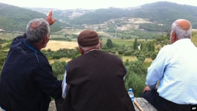 Residents of Güveççi, Turkey, look across the valley to Syria, June 11 2011