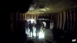 FILE - This image made from video taken on Oct. 22, 2015, from a helmet camera, shows U.S. and Iraqi special forces during a raid inside a makeshift prison in the town of Huwija, 15 kilometers (9 miles) west of the Iraqi city of Kirkuk.
