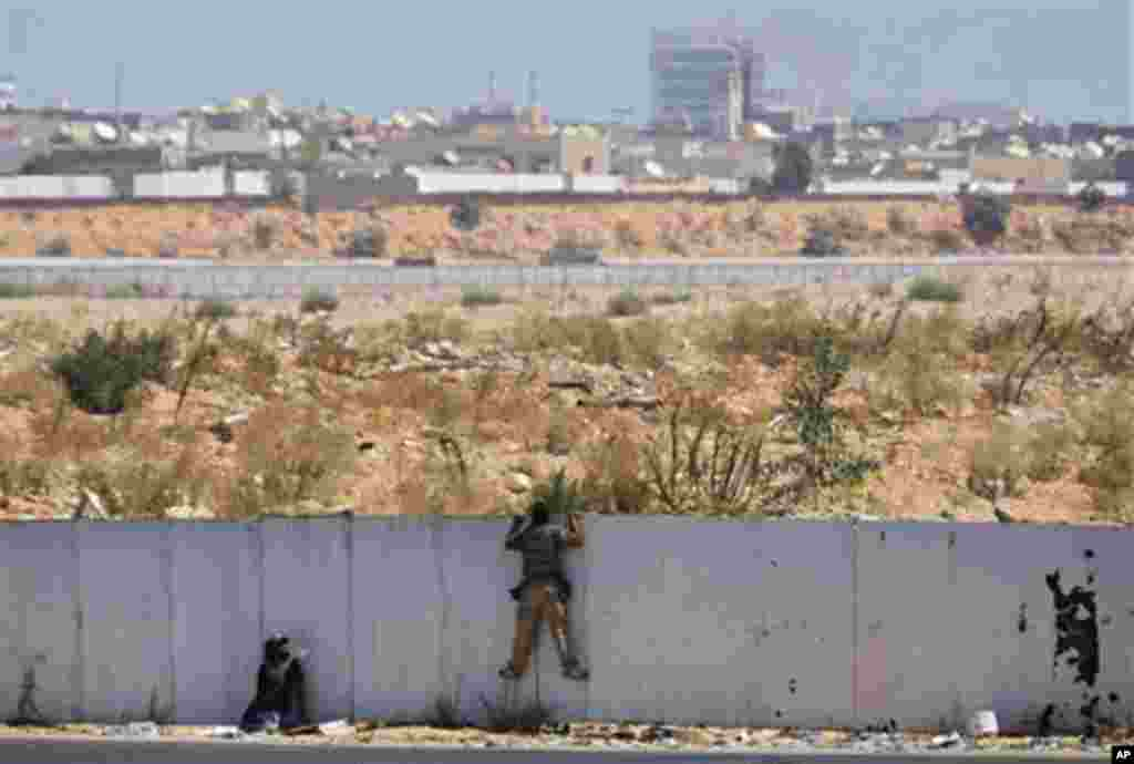 Rebel fighters observe the fighting near the main Moammar Gadhafi compound in Bab Al-Aziziya district in Tripoli, LIbya, Tuesday, Aug. 23, 2011, where some of the heaviest fighting took place. The compound, which has been heavily damaged by NATO airstrike