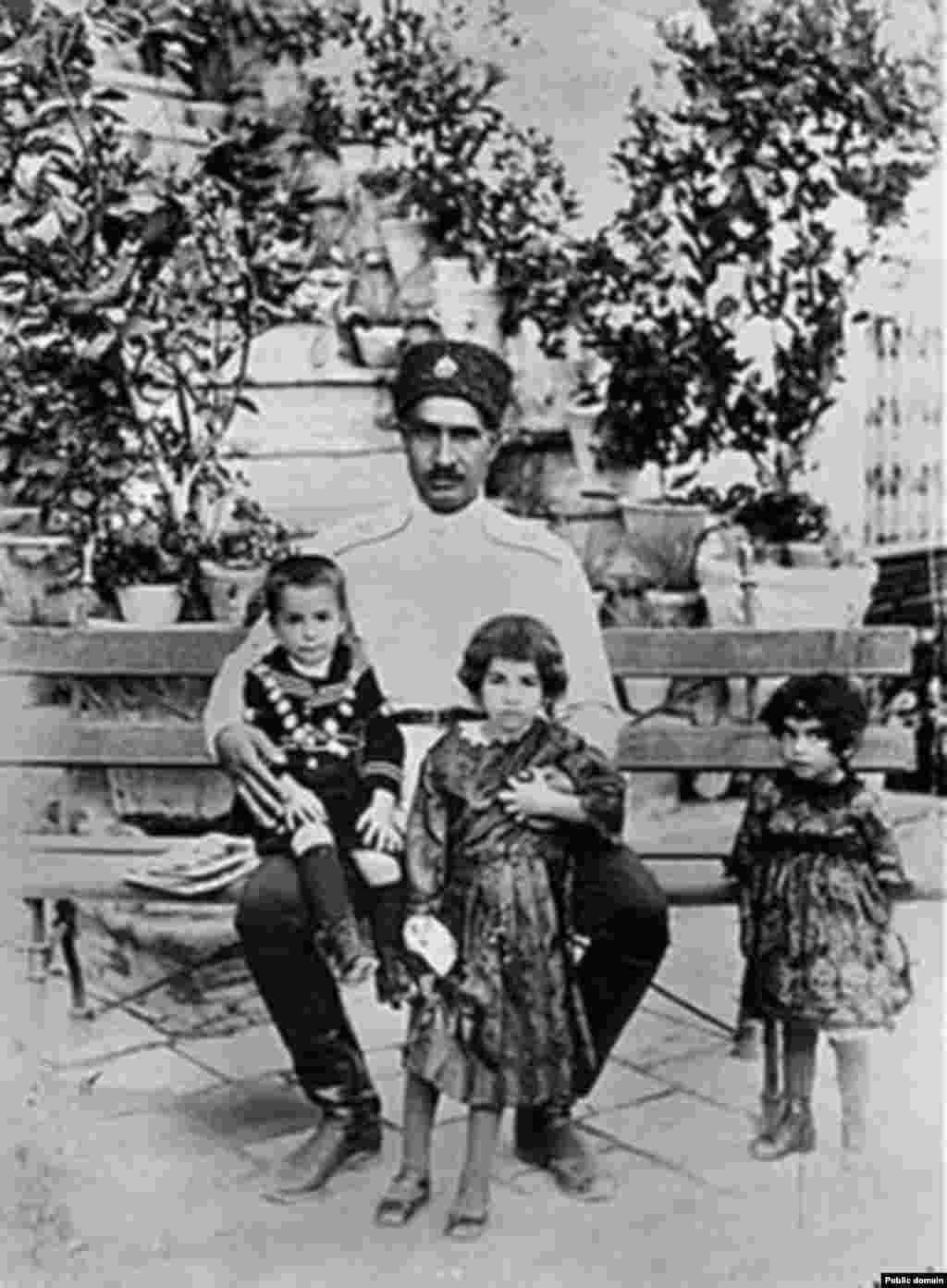 در کنار خواهرانش اشرف و شمس، نشسته بر زانوی رضا شاه