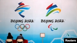 Staff members sit near a board with signs of the 2022 Olympic Winter Games