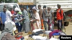 Familia za wakimbizi kutoka Burundi zapiga foleni ili kupokea chakula na nguo kutoka kwa Baraza la Umoja wa mataifa kuhusu haki za binadamu katika eneo la Uvira, Kivu Kusini, nchini DRC mwezi Mei mwaka wa 2014.