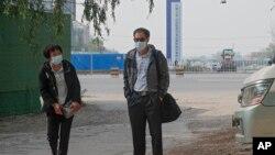 北京公益志願者陳玫的母親(左)和北京公益志願者蔡偉的父親為旁聽他們儿子的庭審到達北京一家法院外。 (2021年5月11日)