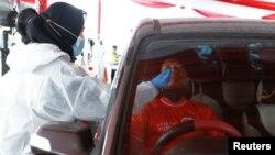 Petugas kesehatan melakukan tes swab kepada pengemudi mobil di Cikarang, Bekasi saat warga kembali ke Jakarta pasca Idul Fitri lalu (foto: dok).