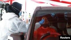 Seorang nakes mengenakan APD saat melakukan tes swab COVID-19 dari pengemudi kendaraan yang kembali ke Ibu Kota Jakarta seusai mudik lebaran di Cikarang, Bekasi, 17 Mei 2021. (REUTERS/Ajeng Dinar Ulfiana)