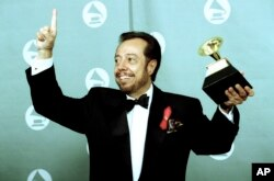 """Sergio Mendes poses with his Grammy at the Grammy Awards ceremony held at the Shrine Auditorium in Los Angeles, Ca., February 24, 1993. Album """"Brasileiro"""" Mendes was selected as the winner of the 1993 world music album of the year. (AP Photo/Reed Saxon)"""