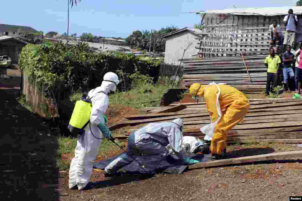 Health workers remove the body of a woman who died from the Ebola virus in the Aberdeen district of Freetown, Sierra Leone, Oct.14, 2014.