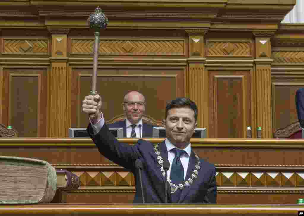 The new Ukrainian President Volodymyr Zelenskiy holds up a mace, the Ukrainian symbol of power, during his inauguration ceremony in Kyiv.