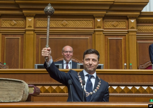 "The new Ukrainian President Volodymyr Zelenskiy holds up a mace or ""bulava,"" the Ukrainian symbol of power, during his inauguration ceremony in Kyiv, Ukraine, May 20, 2019."