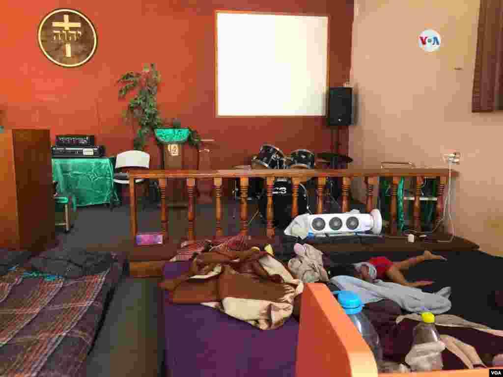 Una niña centroamericana duerme en esta iglesia convertida en dormitorio para familias inmigrantes quienes están esperando su turno para entrar a EE.UU. en México.Photo: Celia Mendoza - VOA.