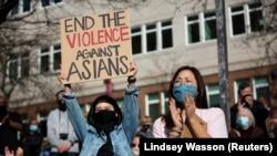 Dawn Cheung dan Victoria Do bertepuk tangan saat memprotes kejahatan kebencian anti-Asia, Washington, A.S. 13 Maret 2021. (Foto: REUTERS/Lindsey Wasson)