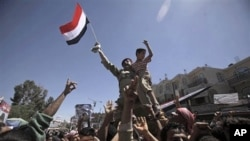 Yemeni army officer raised aloft by anti-government protestors holds a boy and waves his national flag during a demonstration demanding the resignation of Yemeni President Ali Abdullah Saleh, in Sanaa,Yemen, April 4, 2011