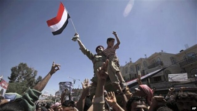 A Yemeni army officer is raised aloft by anti-government protesters during a demonstration demanding the resignation of Yemeni President Ali Abdullah Saleh, in Sana'a, April 4, 2011