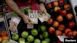 극심한 인플레이션이 진행중인 베네수엘라 수도 카라카스 시장 상인이 지난 7일 물건 값을 받은 뒤 거스름돈을 계산하고 있다.
