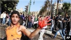 Un jeune manifestant montre sa main recouverte de sang, près de la Place Tahrir, le 18 décembre 2011