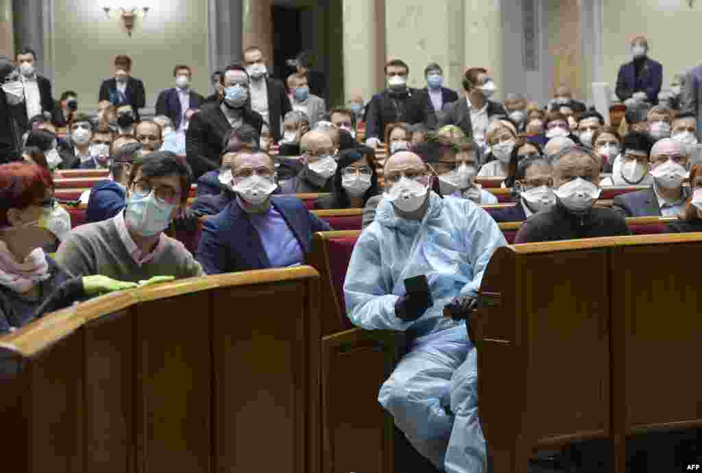 Ukrainian lawmakers wearing face masks to protect against coronavirus attend an extraordinary parliamentary session in Kyiv.